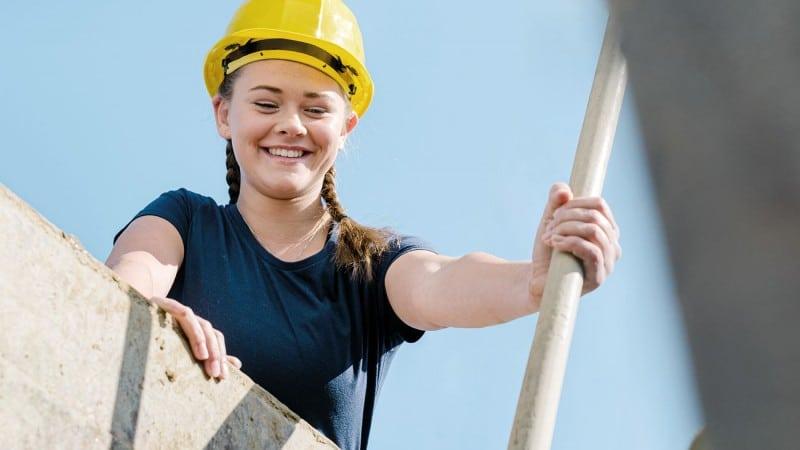 Junge Frau mit Bauhelm bei der Arbeit auf der Baustelle