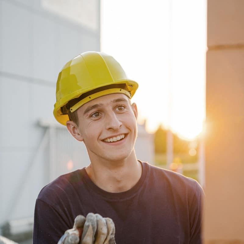 Junger Mann mit Bauhelm beim Verputz auf der Baustelle