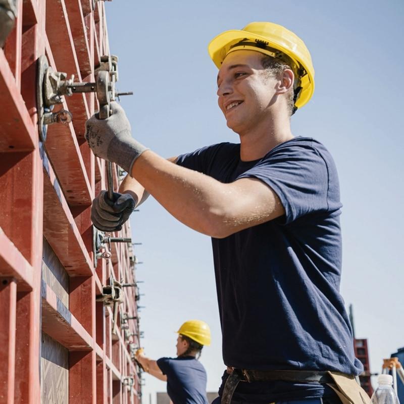 Junger Mann mit Bauhelm bei der Betonbau-Arbeit
